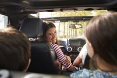 Famiglia che guida in automobile senza coperchio sul viaggio stradale della campagna fotografie stock