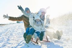 Famiglia che guida slitta sulla neve immagine stock