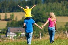 Famiglia che ha camminata sul prato Immagini Stock Libere da Diritti