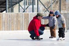 Famiglia che ha divertimento alla pista di pattinaggio pattinante Fotografia Stock
