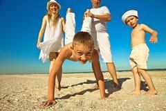 Famiglia che ha divertimento alla spiaggia Immagine Stock