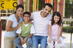 Famiglia che ha divertimento in campo da giuoco Immagini Stock