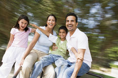Famiglia che ha divertimento sulla rotonda di filatura immagine stock