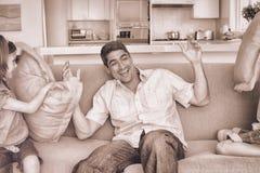 Famiglia che ha lotta di cuscino sul sofà illustrazione vettoriale