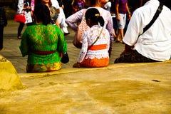 Famiglia che indossa abbigliamento locale tradizionale che aspetta sul tempio fotografie stock