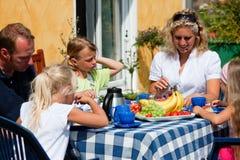 Famiglia che mangia caffè nel giardino Fotografia Stock