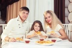 Famiglia che mangia cena ad un tavolo da pranzo, tavola rotonda, pizza, arancia, casa fatta di legno fotografie stock
