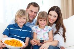 Famiglia che mangia le patatine fritte sul sofà Fotografia Stock Libera da Diritti