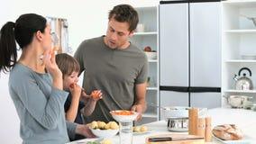 Famiglia che mangia le verdure mentre preparano il pranzo stock footage