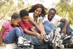 Famiglia che mette sopra nella riga pattini in sosta Fotografie Stock Libere da Diritti