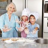 Famiglia che mostra le mani con farina nella cucina Fotografie Stock