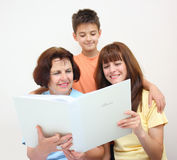 Famiglia che osserva l'album di foto Immagini Stock