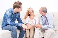 Famiglia che parla nel salone Fotografia Stock Libera da Diritti
