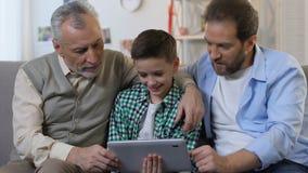 Famiglia che per mezzo insieme della compressa a casa, regalo di compleanno per il ragazzino, generazione video d archivio