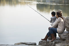 Famiglia che pesca fuori delle rocce nel lago Fotografie Stock Libere da Diritti