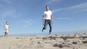 Famiglia che pilota un aquilone sulla spiaggia archivi video