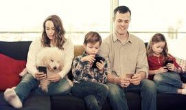Famiglia che plaing con i telefoni cellulari fotografia stock