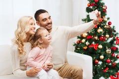 Famiglia che prende selfie con lo smartphone al natale immagine stock