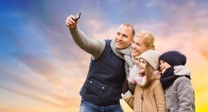 Famiglia che prende selfie dallo smartphone sopra il cielo fotografia stock libera da diritti
