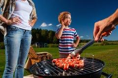 Famiglia che prepara le salsiccie su una griglia Fotografia Stock Libera da Diritti