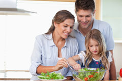 Famiglia che prepara un'insalata Immagine Stock