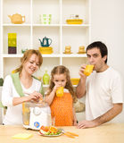 Famiglia che produce e che beve la spremuta della frutta fresca Immagini Stock