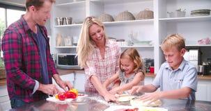 Famiglia che produce insieme pizza in cucina archivi video
