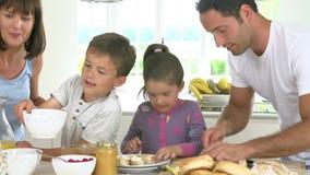 Famiglia che produce insieme prima colazione in cucina stock footage
