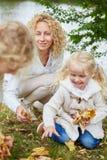 Famiglia che raccoglie le foglie in natura fotografia stock libera da diritti