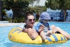 Famiglia che riposa sull'anello di nuotata Fotografia Stock Libera da Diritti