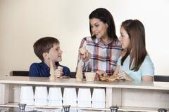 Famiglia che sceglie fra i coni e le tazze al contatore immagini stock