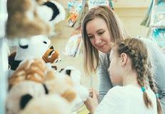 Famiglia che sceglie giocattolo nel deposito dei bambini Fotografie Stock Libere da Diritti