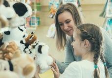 Famiglia che sceglie giocattolo nel deposito dei bambini Fotografia Stock Libera da Diritti