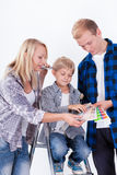 Famiglia che sceglie un colore per la parete di verniciatura Immagini Stock Libere da Diritti