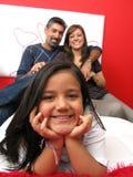 Famiglia che si adagia nella lettura della base Fotografie Stock Libere da Diritti
