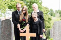 Famiglia che si addolora alla tomba sul cimitero fotografia stock