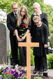 Famiglia che si addolora alla tomba sul cimitero immagine stock