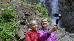 Famiglia che si cattura con la piccola macchina fotografica personale alla cascata della montagna video d archivio