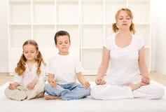 Famiglia che si distende con l'yoga Fotografie Stock Libere da Diritti