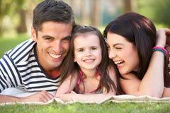 Famiglia che si distende nel giardino di estate Fotografie Stock Libere da Diritti