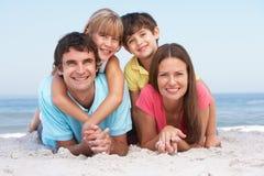 Famiglia che si distende sulla festa della spiaggia Immagini Stock