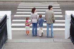 Famiglia che si leva in piedi crosswalk vicino, dietro Fotografie Stock Libere da Diritti