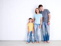 Famiglia che si leva in piedi insieme vicino alla parete vuota Immagini Stock Libere da Diritti