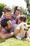 Famiglia che si rilassa nel giardino con il cane di animale domestico Fotografie Stock Libere da Diritti