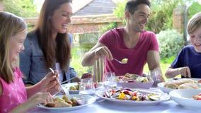 Famiglia che si siede all'aperto intorno al cibo della Tabella archivi video