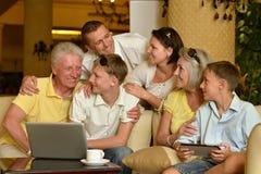 Famiglia che si siede con i dispositivi digitali Fotografie Stock