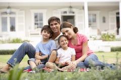 Famiglia che si siede fuori della Camera sul prato inglese fotografie stock libere da diritti