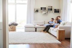Famiglia che si siede insieme su Sofa At Home Watching TV fotografia stock libera da diritti