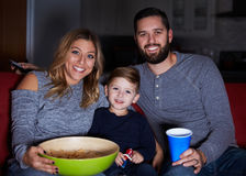 Famiglia che si siede insieme sulla televisione di sorveglianza del sofà Fotografie Stock Libere da Diritti