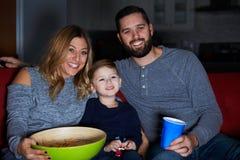 Famiglia che si siede insieme sulla televisione di sorveglianza del sofà Immagini Stock Libere da Diritti